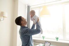 Jonge mens die een baby werpen stock foto