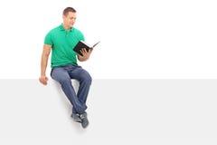 Jonge mens die een boek gezet op een uithangbord lezen Stock Foto's