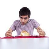 Jonge mens die een cake eet Stock Afbeeldingen