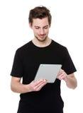 Jonge mens die een de tabletpc houden van het aanrakingsstootkussen stock foto's