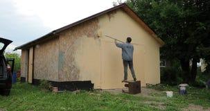 Jonge mens die een garage met een rol in de dagtijdtijdspanne video4k schilderen stock videobeelden