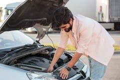 Jonge mens die een gebroken auto proberen te herstellen royalty-vrije stock foto
