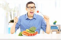 Jonge mens die een gezonde maaltijd thuis eten Stock Afbeelding