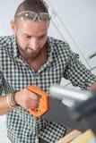 Jonge mens die een handsaw gebruiken royalty-vrije stock foto