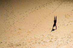 Jonge mens die een handstand op het zand uitvoeren stock afbeeldingen