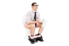 Jonge mens die een harde tijd op het toilet hebben Royalty-vrije Stock Afbeeldingen