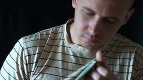 Jonge mens die een honderd-dollar rekening snuiven stock footage