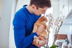 Jonge mens die een kat thuis houden dichtbij de orchidee stock afbeelding