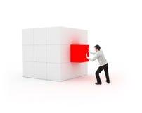 Jonge mens die een kubus voor voltooiing plaatsen Stock Foto