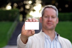 Jonge mens die een leeg adreskaartje 2 houdt Stock Afbeeldingen