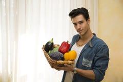 Jonge mens die een mand van verse groenten houden, gezonde voedingconcept Stock Afbeelding
