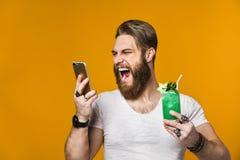 Jonge mens die een multicolored cocktail houden stock foto's