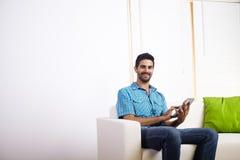 Jonge mens die een PC van de Tablet met behulp van stock fotografie