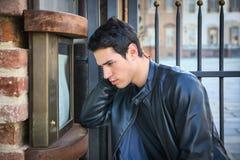 Jonge mens die een publiciteit op een raad lezen Stock Foto's