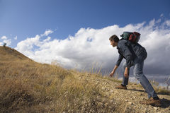 Jonge mens die een rots beklimt stock foto's