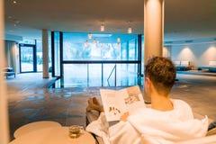 Jonge mens die een rust in het KUUROORD hebben door de open pool in een robe Lezingstijdschrift royalty-vrije stock afbeelding