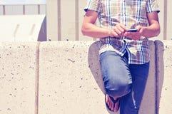 Jonge mens die een smartphone in openlucht gebruiken Stock Foto