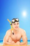 Jonge mens die een snorkelend masker op een strand dragen Stock Afbeelding