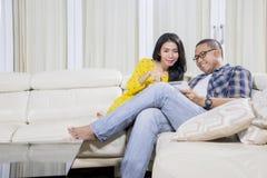 Jonge mens die een tablet met zijn vrouw thuis gebruiken royalty-vrije stock foto's