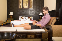 Jonge mens die een tabletpc in een Aziatische hotelruimte met behulp van Royalty-vrije Stock Foto