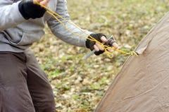 Jonge mens die een tent in het hout a zetten Stock Fotografie