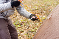 Jonge mens die een tent in het hout a zetten Stock Foto