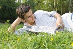 Jonge mens die een tijdschrift in het park leest Stock Afbeelding
