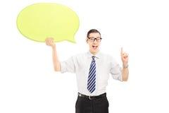 Jonge mens die een toespraakbel houden en met zijn vinger gesturing Stock Afbeeldingen
