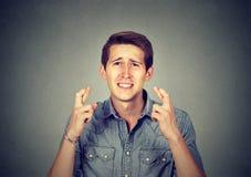 Jonge mens die een wens maken die zijn vingers gekruist houden royalty-vrije stock afbeeldingen
