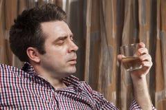 Jonge mens met wijnglas, die gedronken kijken stock foto's