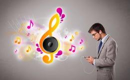 Jonge mens die en aan muziek met muzieknoten zingen luisteren Stock Fotografie