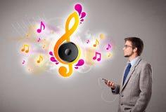 Jonge mens die en aan muziek met muzieknoten zingen luisteren Stock Afbeeldingen