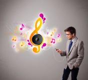 Jonge mens die en aan muziek met muzieknoten zingen luisteren Stock Foto's