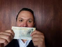jonge mens die en een Deens bankbiljet van 100 kronen tonen houden stock afbeelding