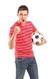 Jonge mens die en een voetbal toejuicht houdt Royalty-vrije Stock Foto's