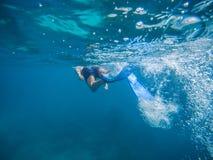 Jonge mens die en met masker en vinnen in duidelijk blauw water zwemmen snorkelen stock foto's