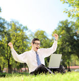 Jonge mens die en op TV op laptop in een park op su toejuichen letten Stock Afbeelding
