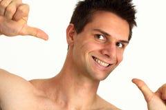 Jonge mens die en op zich glimlacht richt Stock Fotografie