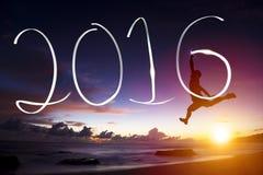 Jonge mens die en 2016 springen trekken op strand stock fotografie