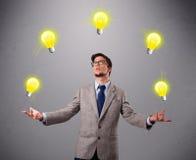 Jonge mens die en zich met gloeilampen bevinden jongleren met Stock Afbeelding