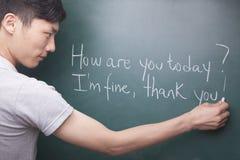 Jonge mens die Engelse zinnen op het bord schrijven Royalty-vrije Stock Fotografie