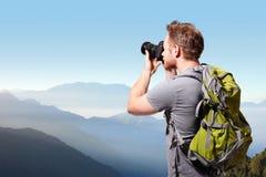 Jonge mens die foto bovenop berg nemen Stock Foto