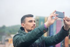 Jonge mens die foto met zijn telefoon op het dak nemen royalty-vrije stock foto's