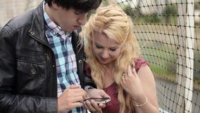 Jonge mens die foto's op mobiele telefoon van zijn meisje nemen die pret hebben bij de straat stock video