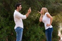 Jonge mens die foto van zijn girfriend het kussen nemen Royalty-vrije Stock Afbeeldingen