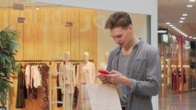 Jonge mens die, gebruikend smartphone terwijl het winkelen bij de wandelgalerij glimlacht stock footage