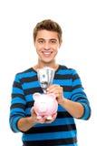 Jonge mens die geld in spaarvarken zet stock foto's
