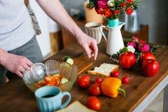 Jonge mens die gezond ontbijt maken stock afbeelding