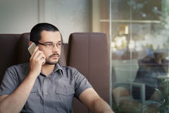 Jonge Mens die Glazen dragen die op de Telefoon spreken Stock Fotografie