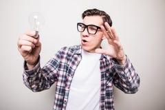jonge mens die in glazen kleine gloeilamp houden Stock Foto's